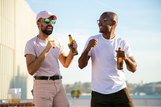 two men on a rooftop in the sun laughing and enjoying beers and snacks together