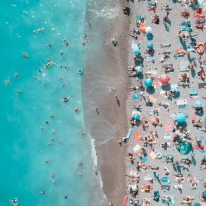 crowded white sand beach with crystal blue ocean water