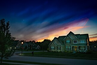 suburban family home at sunset with a divided sky framing the house with light