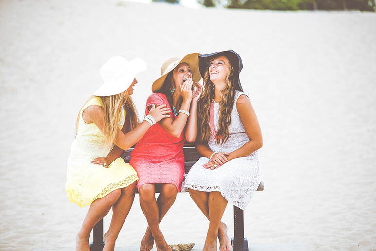 photo: three young women siting on a bench talking and laughing in sunhats