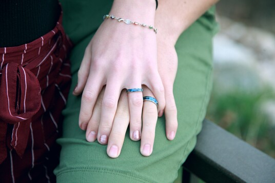photo of two hands with matching turquois engagement rings