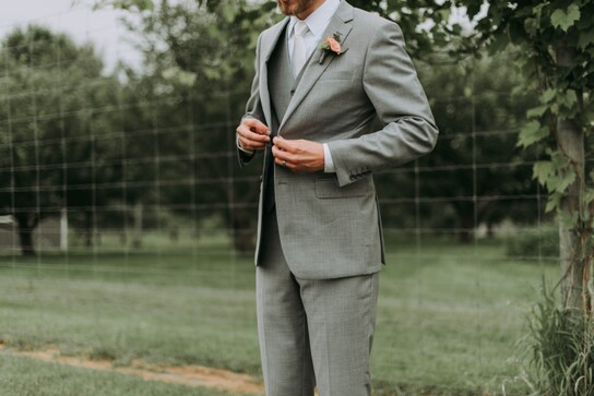 photo of a groom in a grey suit standing in a field buttoning his jacket