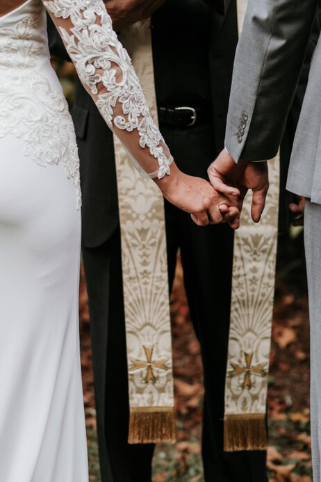 close up photo of couple holding hands in front of a priest