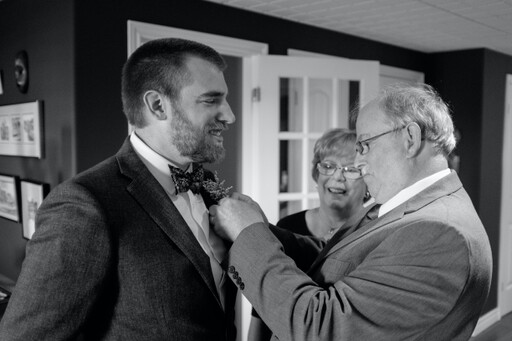photo of a father pinning a flower on his son the groom while mom watches and smiles
