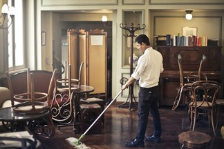 professional cleaner mopping a wooden floor in a retro-looking parlor
