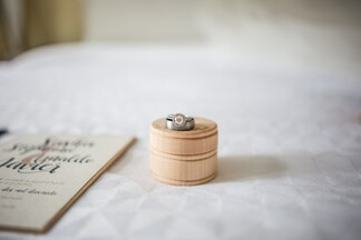 wedding rings on top of a white cloth table with a wedding invitation next to them