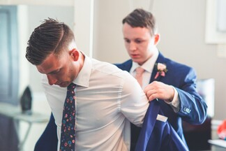 groom putting on his formal coat with the help of a groomsman