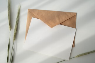 blank invitation card sitting on top of a brown envelope