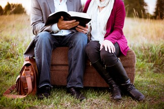 husband and wife reading the bible on an ottoman together
