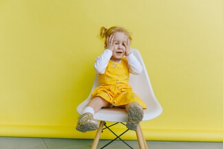 young child with her palms on her face sitting on a white chair with a yellow background