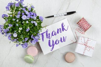 thank you card on marble table with gift box, twine, flowers, and macaroons