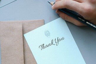 white thank you note atop beige envelope with a writer's hand holding a pencil above it