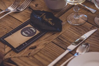 table setting at a wedding with place cards on a wooden table