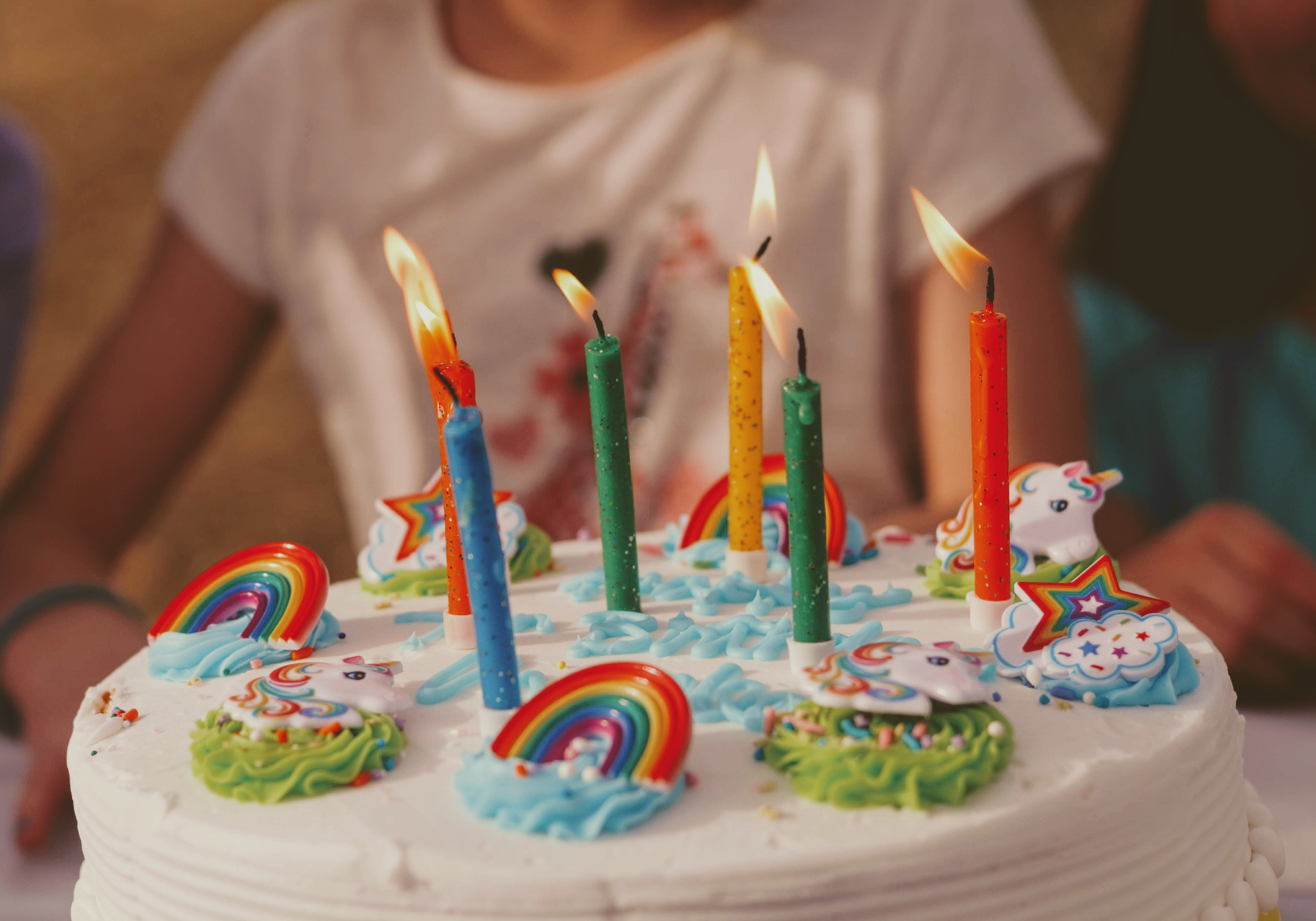 photo: birthday cake with candles, sprinkles and decorations help by little girl