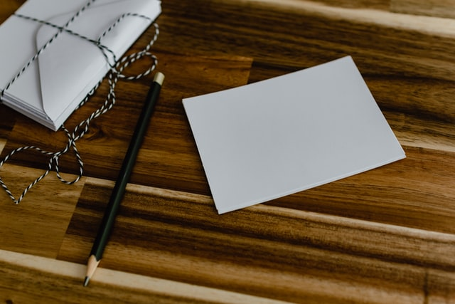 photo: notecard wrapped in string, pencil, and single card sitting on a wood surface