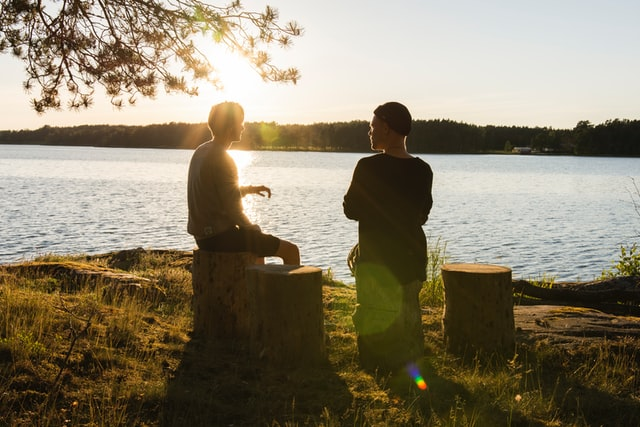 photo: two men sit by a lake talking at sunset