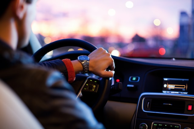 photo: over the shoulder shot of man driving car at dusk with dashboard illuminated