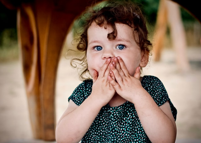 photo: little girl covers her mouth with the oops gesture