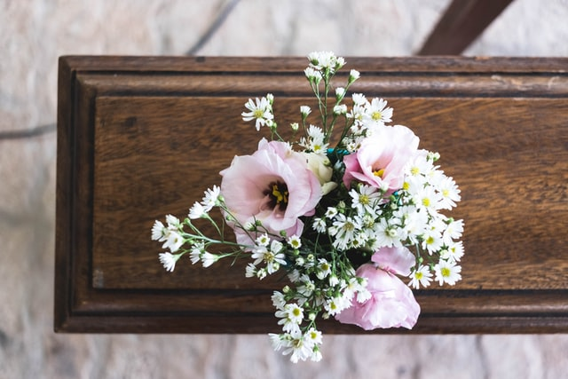 photo: pink and white flowers on a wooden casket shot from above