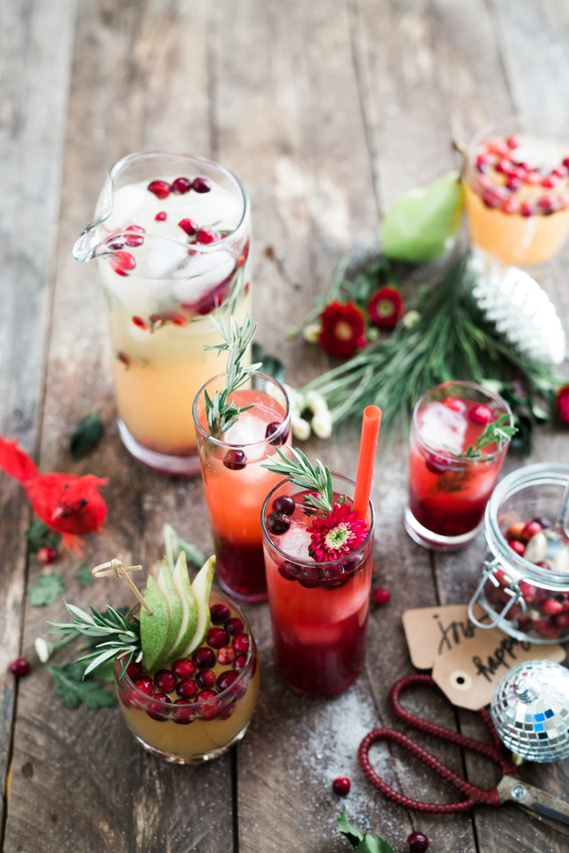 photo: festive mixed drinks with herbs and cranberries on a table with decorations, tags, and scissors.