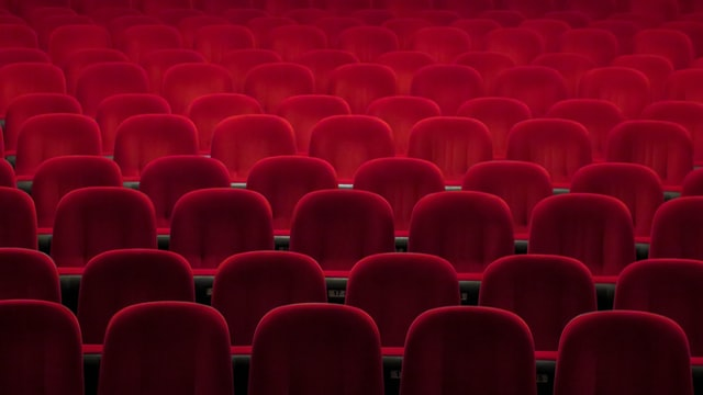 photo: rows of velvet seats in a theater fill the frame