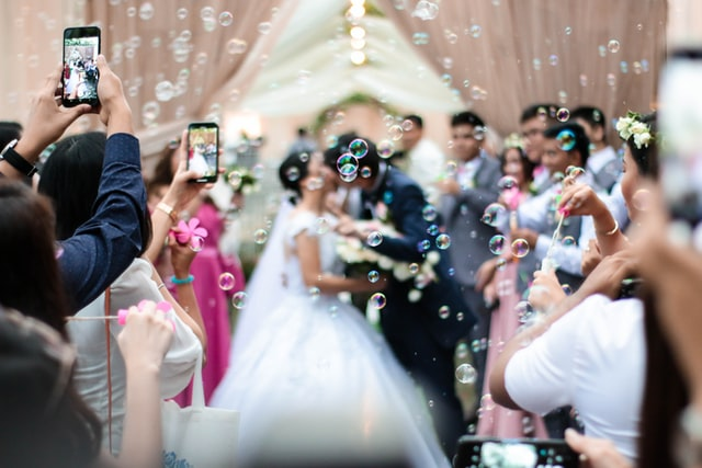 photo: bride and groom kiss amid bubbles while guest hold cell phones and take pictures