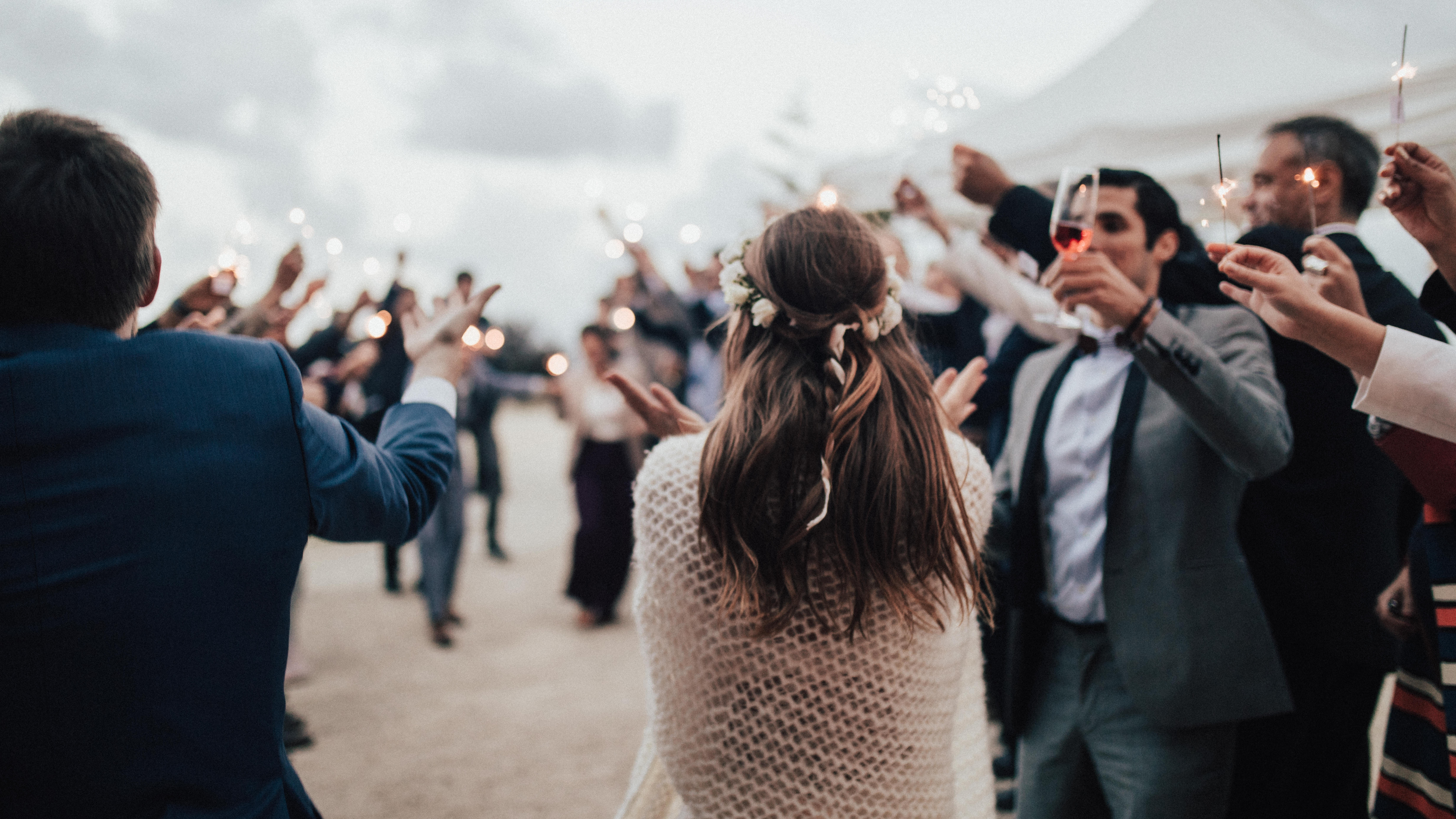 wedding crowd welcomes bride and groom with sparklers