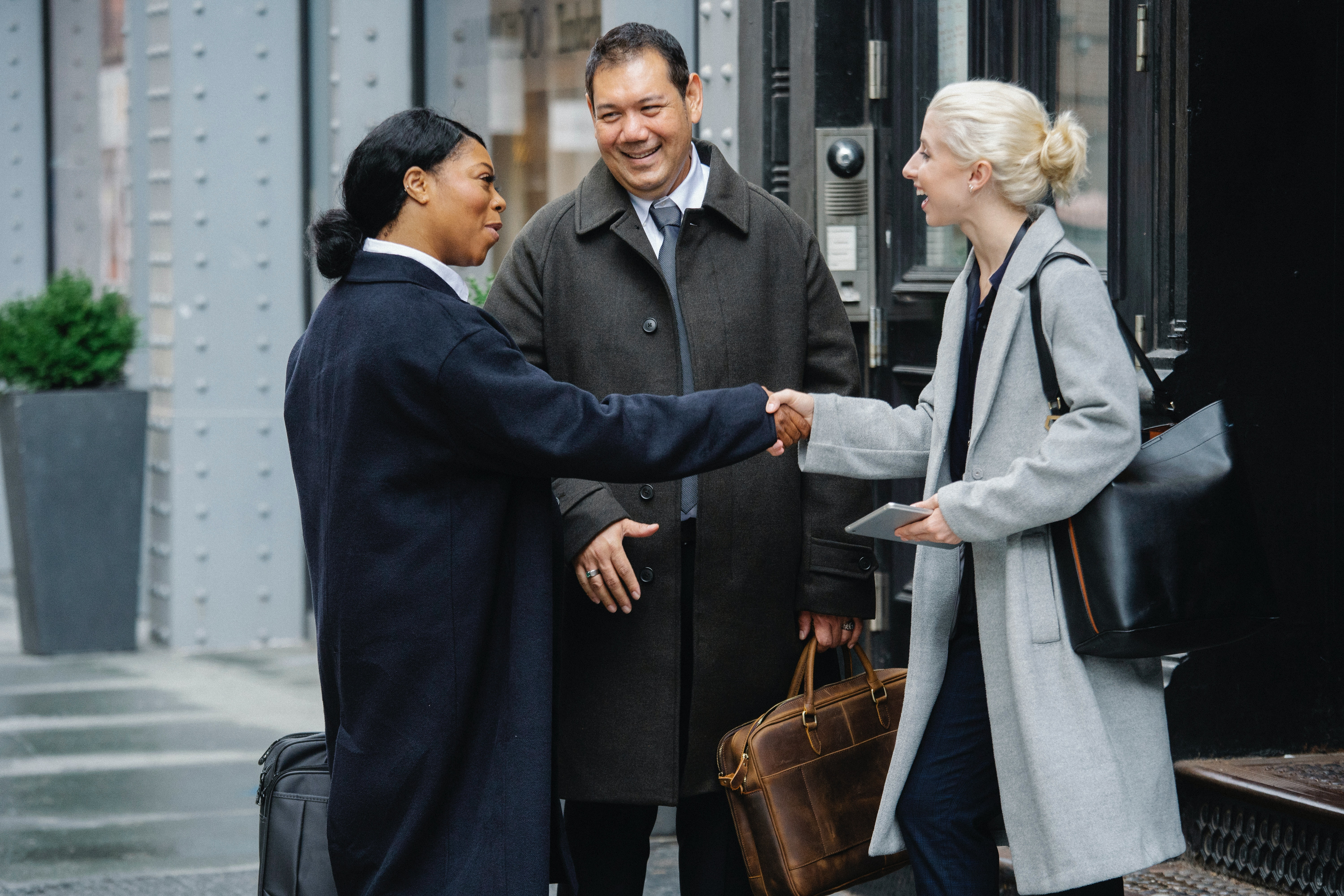 positive diverse colleagues shaking hands after meeting on street