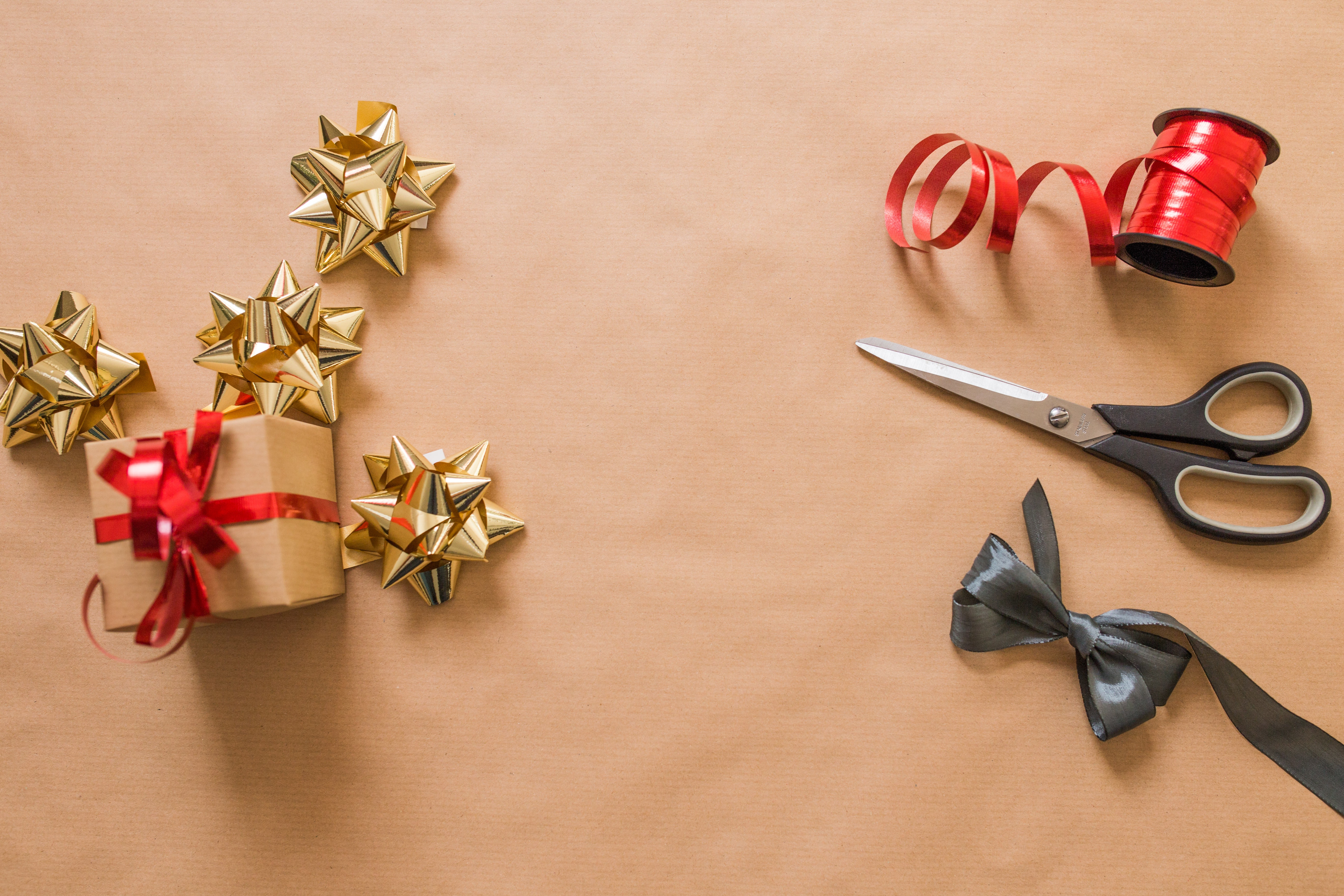 golden bows, red ribbon, and a pair of scissors on top of a light brown background