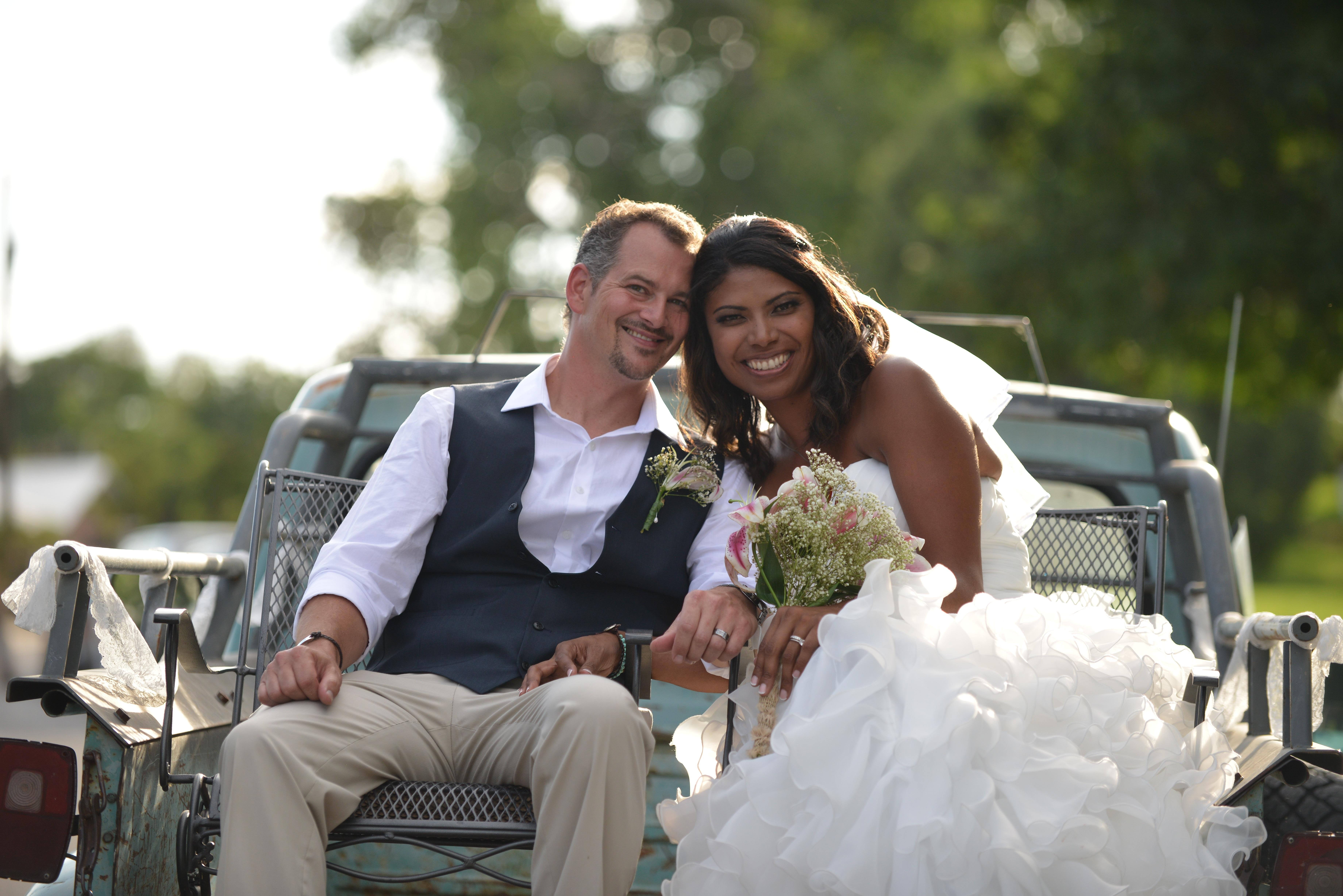 happy newlyweds sitting on the back of a truck