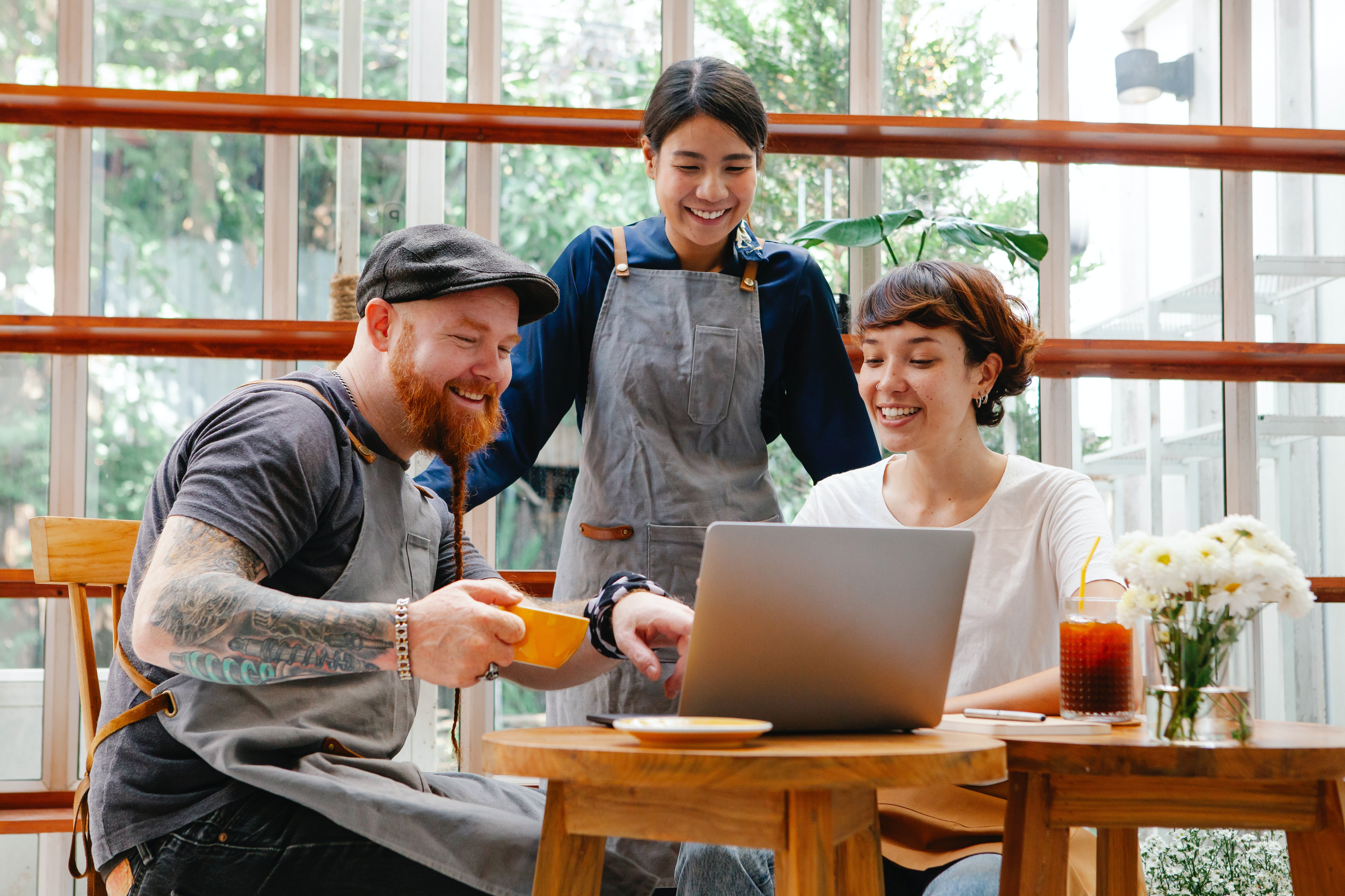 diverse group of friends looking at a computer screen in a cafe