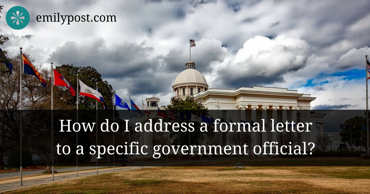 Image of the capitol building from the side front with flags in the foreground and overlay text reading 'how do I address a formal letter to a specific government official?'