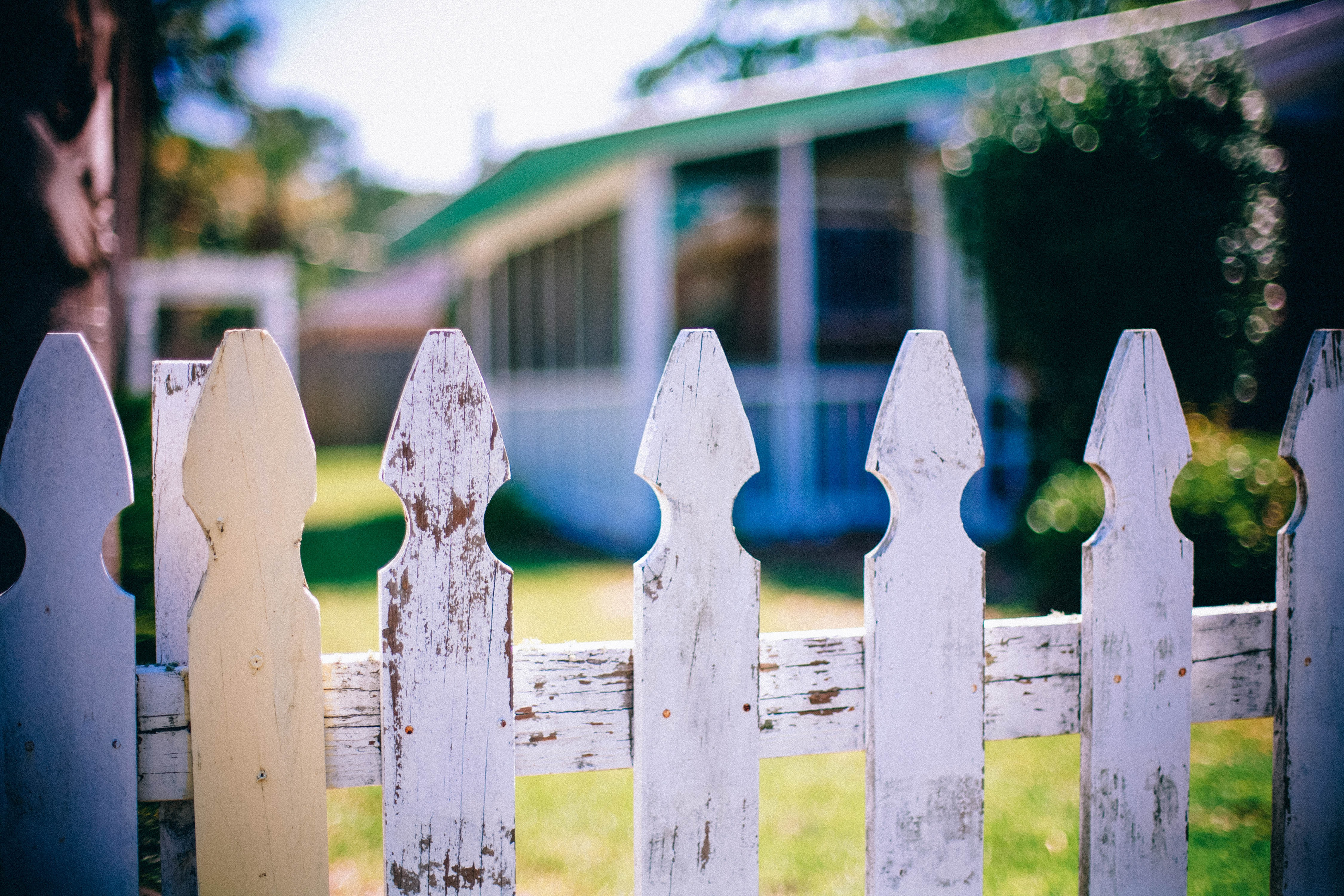 worn white picket fence with white and green home in background
