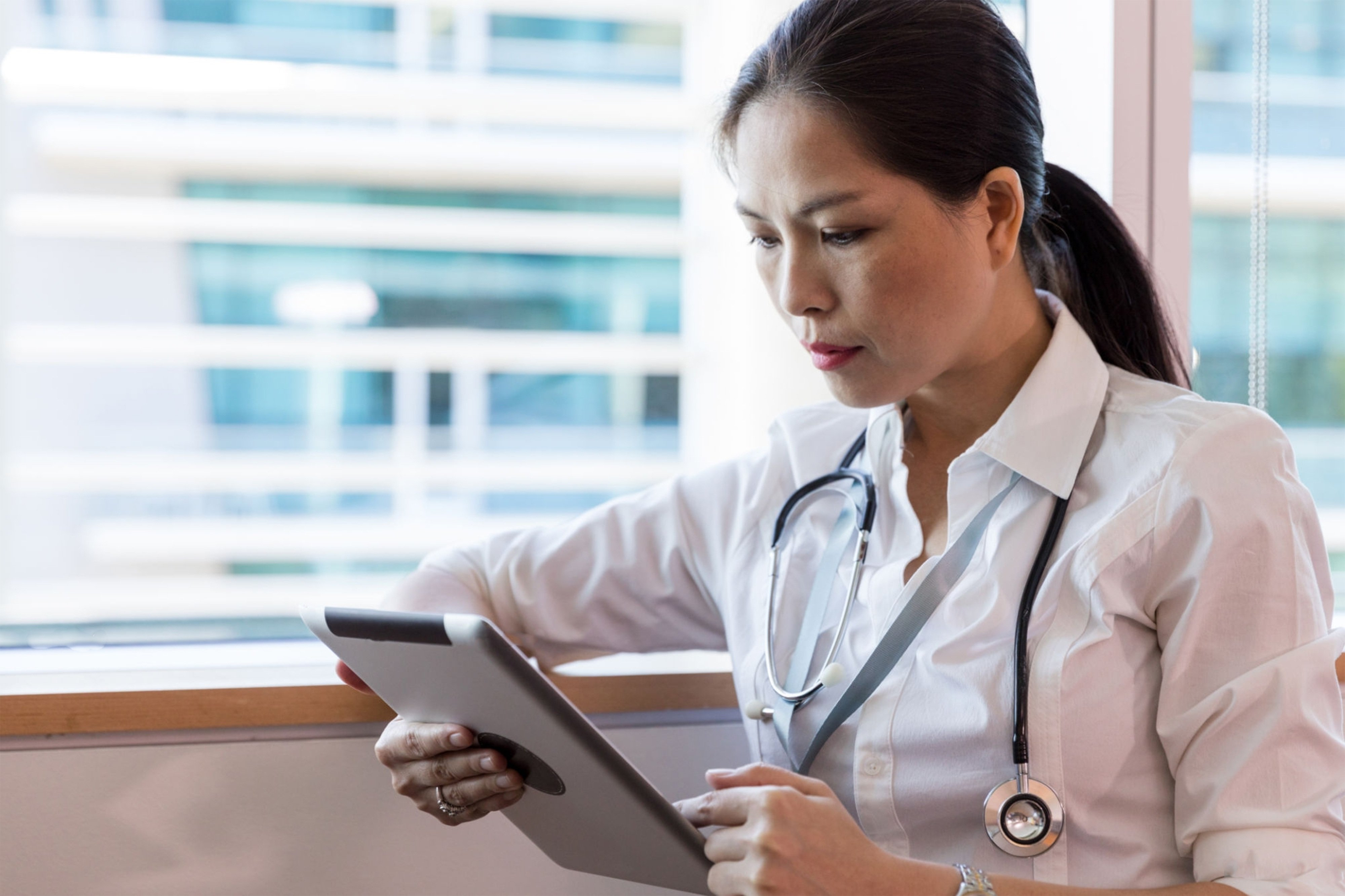 female doctor reviewing information on a tablet