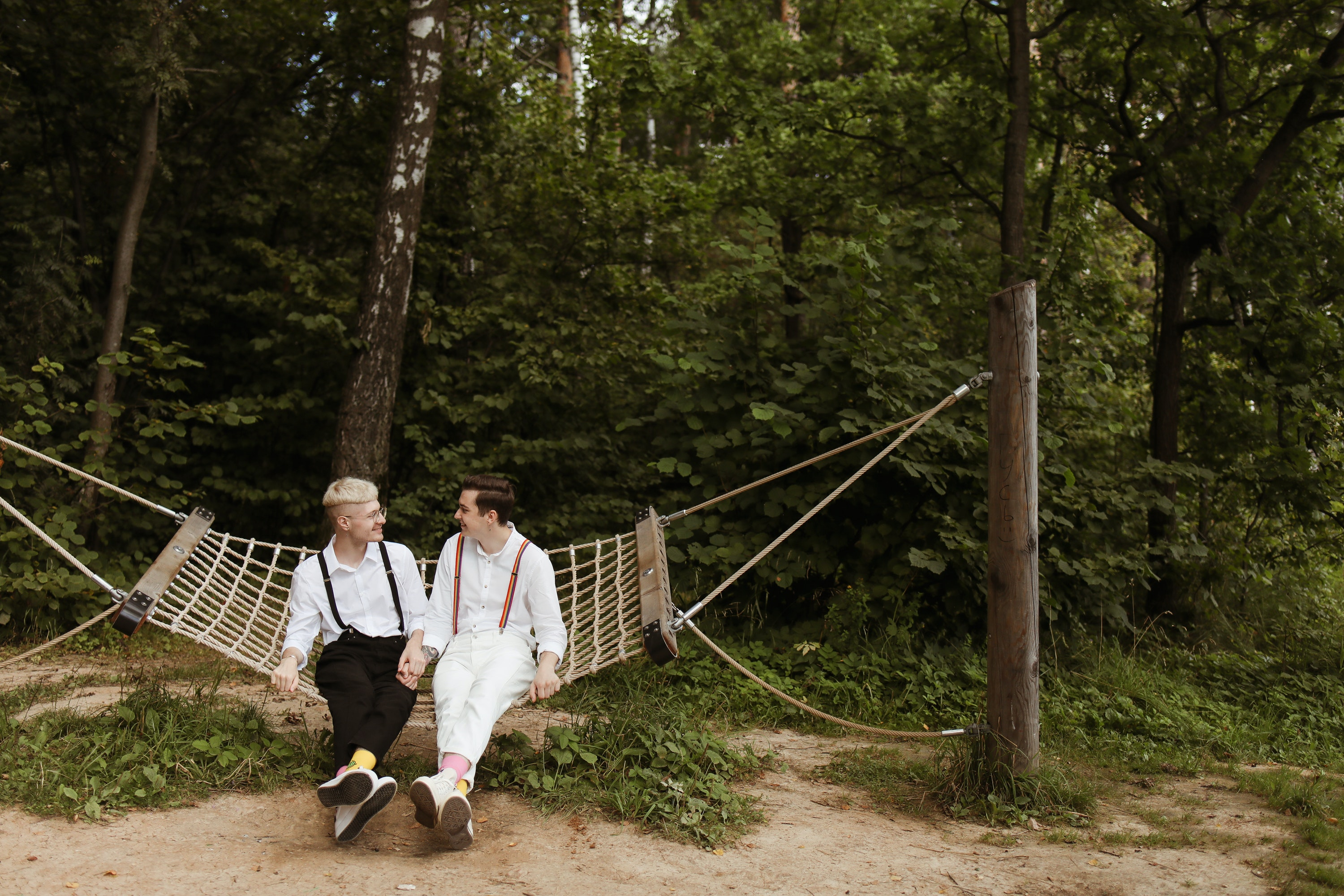 grooms smiling at each other holding hands on a hammock with a green wooded backdrop