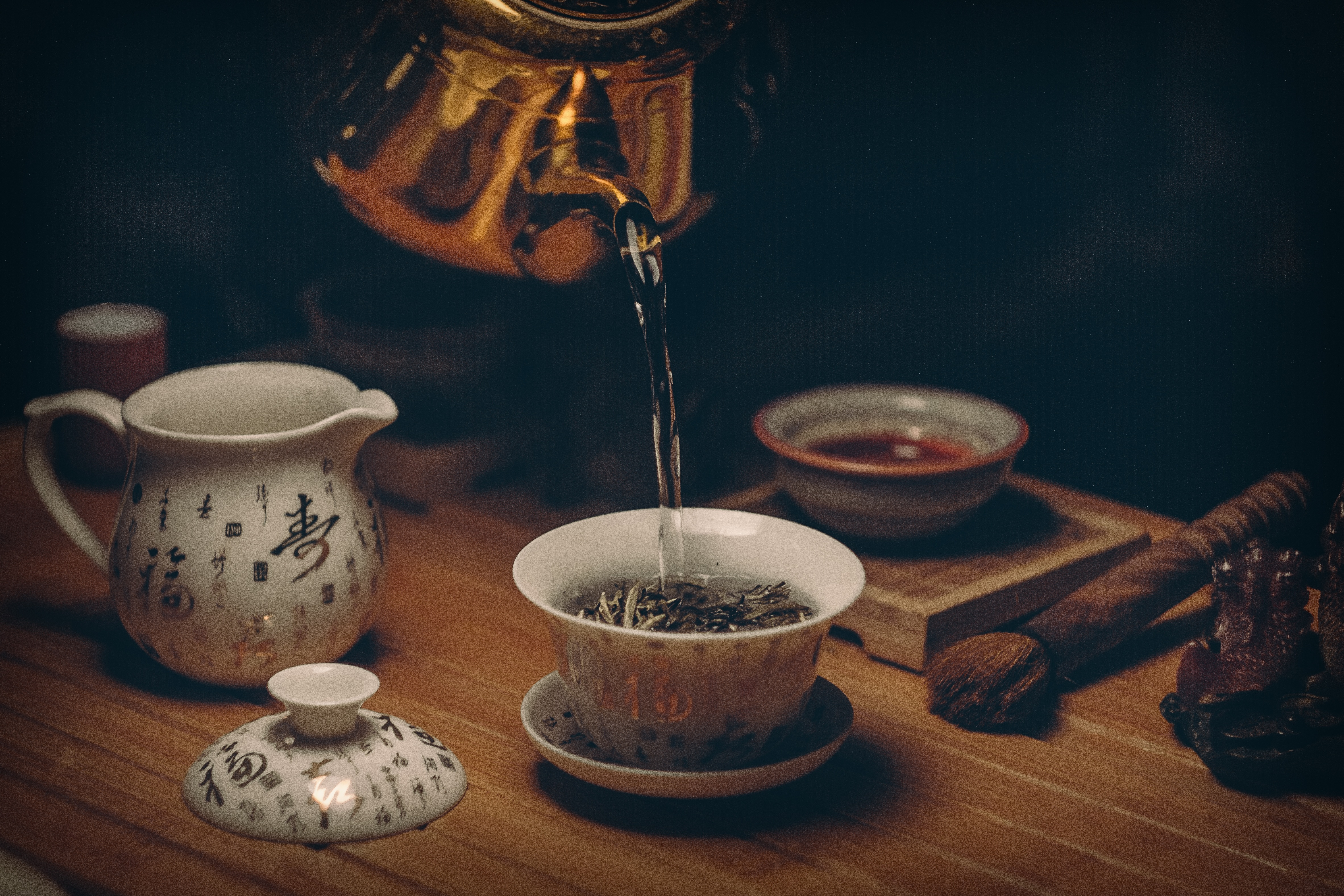 golden kettle pouring hot water into a white teacup atop a wooden table
