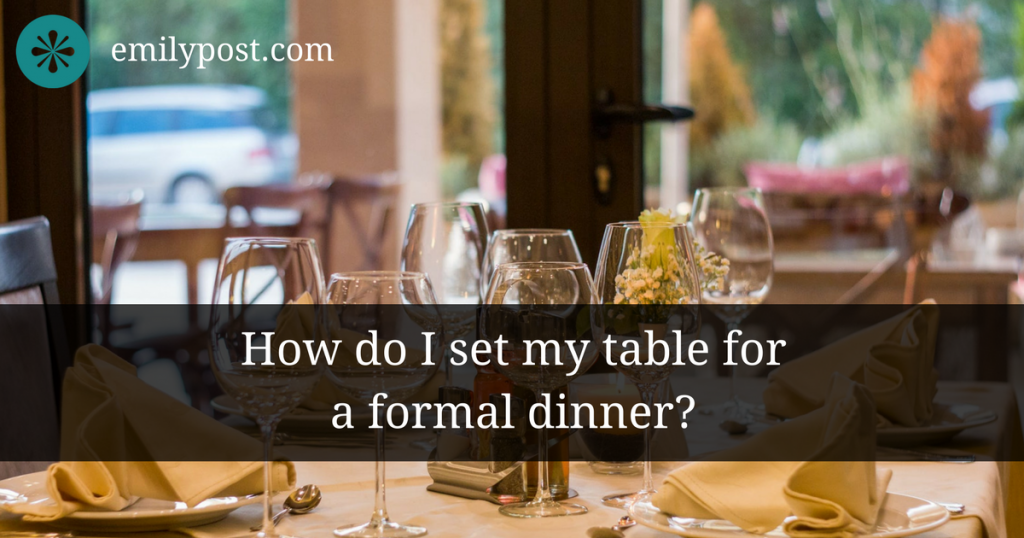 formal place setting on top of white cloth table in a well-lit dining room